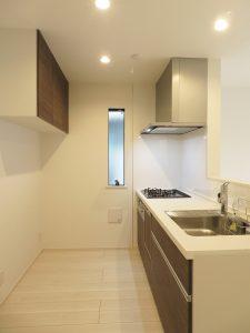 落ち着いた色合いの使いやすいキッチンです。背面に棚があるので、収納スペースが充実。リビングが見渡せて開放感があります。